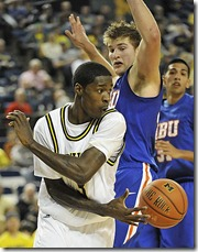 (caption) U-M's Manny Harris dishes a pass around HBU's Mario Flaherty during the second half. Harris led the Wolverines with 25 points and eight rebounds.   ***  The University of Michigan Wolverines defeated the Houston Baptist University Huskies 77-55 at Crisler Arena in Ann Arbor. Photos taken on Friday, November 20, 2009.  ( John T. Greilick / The Detroit News )