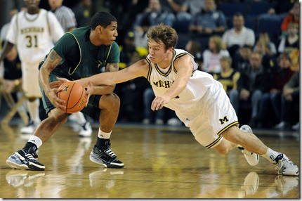 Michigan's Zack Novak, right, dives to try and steel the ball from Northern Michigan University's Raymont McElroy during first half action of Saturday night, November 14th's season opener for the Wolverines at UM's Crisler Arena.  Lon Horwedel | AnnArbor.com