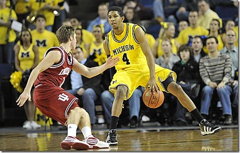 (caption) Michigan guard Darius Morris dribbles between his legs while keeping the ball away from Indiana's Jordan Hulls during the second half.  *** Led by Manny Harris and his 17 second half points, the Michigan Wolverines defeated the Indiana Hoosiers 69-45 at Crisler Arena in Ann Arbor. Photos taken on Thursday, January 14, 2010.  ( John T. Greilick / The Detroit News )